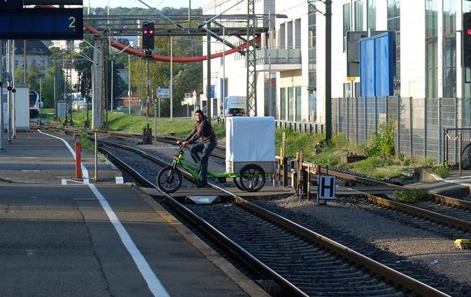 Mit dem Cargobike über ebenerdigen Gleisübergang.